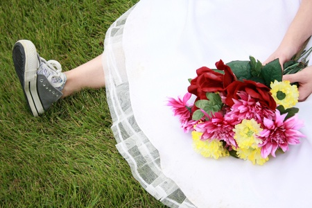 A bride wearing running shoes and a wedding gown