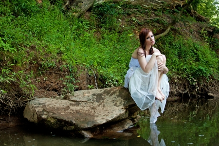 wet dress: Woman sitting on a rock by the river