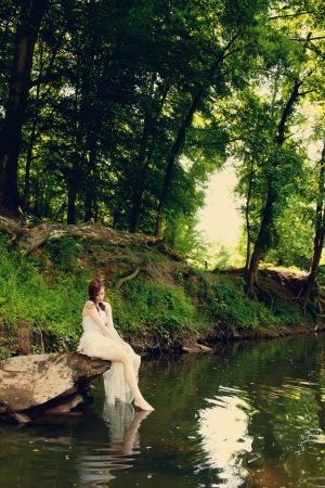A bride sitting on a rock on a riverbank photo