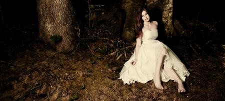 Eine Braut sitzt unter einem Baum im dunklen Wald Standard-Bild - 13845651