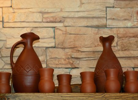 Clay jugs and clay cups on a shelf