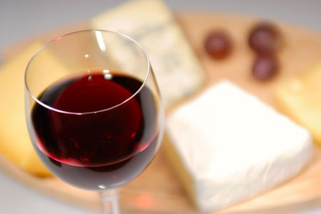 Glass of red wine and cheese plate photo