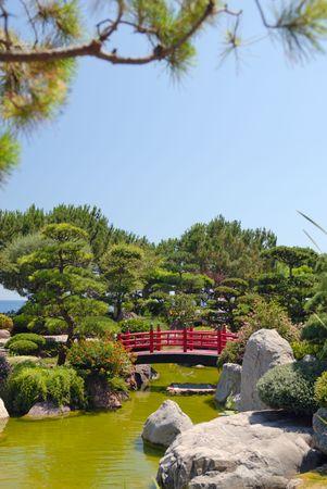 Japanese red bridge in zen garden photo