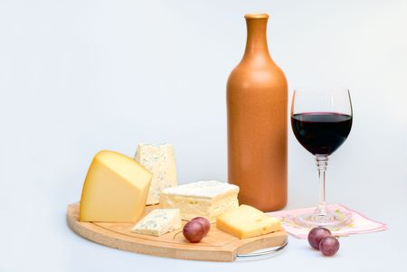 cheeseboard: Glass of red wine bottle and cheese plate Stock Photo
