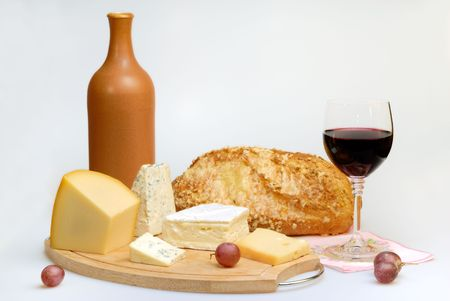 Glass of red wine bottle and cheese plate Stock Photo