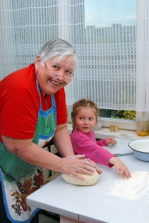 Grandmother and granddaughter knead the dough