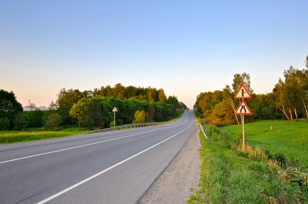 Asphalt road with signs on roadside and forest around in sunset light Stock Photo - 11938090
