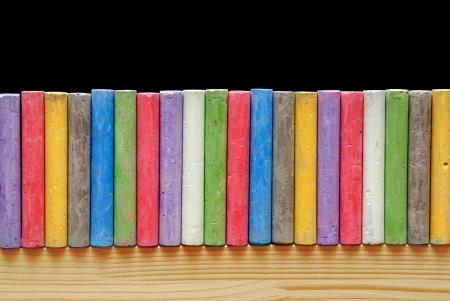 Color chalks arranged in line on blackboard photo