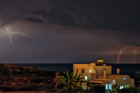 Lightning storm over sea and beach house photo