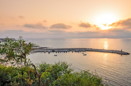 Sunset over sea bay for fishing boats photo