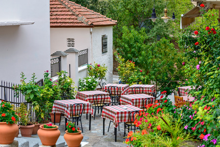 Restaurant tables on street terrace with beautifull flowers around photo