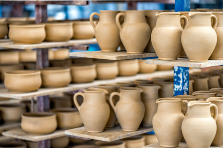 Shelves with ceramic dishware in pottery workshop Stock Photo