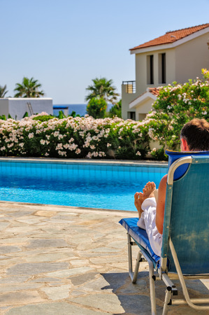 Man relax on deck chair near swimming pool photo