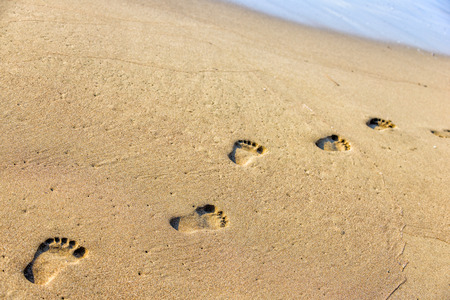 Footsteps on the sand beach photo
