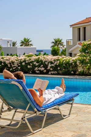 Man relax and read book on deck chair near swimming pool photo