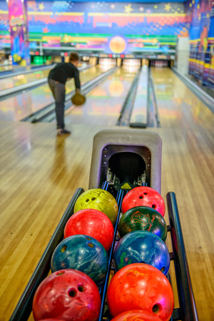 bowling alley: Bowling balls and silhouette of player on blurred background Editorial