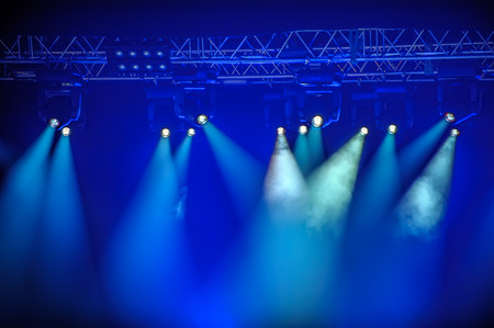 Blue stage spotlights hanging on lighting pipe systems photo
