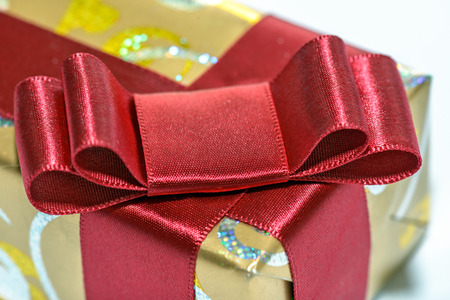 wrapped gift: Closeup view of red ribbon and bow on wrapped gift
