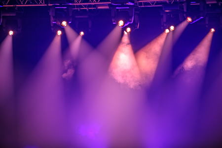 stage lighting: Purple stage spotlights hanging on lighting pipe systems Stock Photo