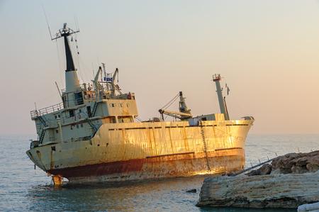 Cargo ship aground near rocky coast in sunset light Stock Photo