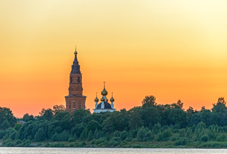 Old orthodox cathedral on bank of the Volga river in Russia over sunset sky