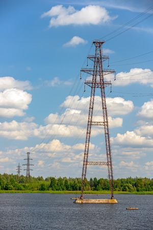 Power lines, towers and pylons over river   Stock Photo
