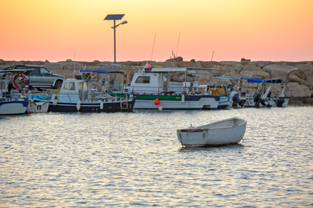 Sunset over fishing boats in harbor Stock Photo