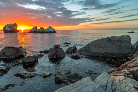 Beautiful sunset over sea and stone shore