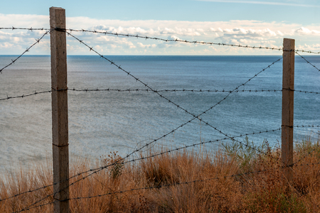Barbed wire fence on sea coast Stock Photo