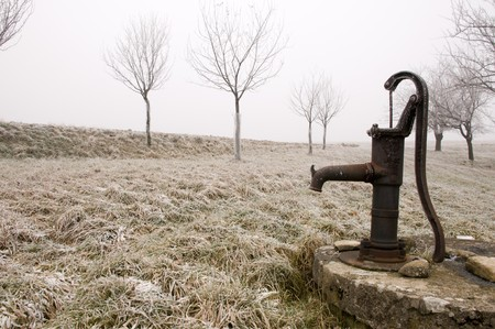 winter field: Old rusty water pump on the countryside in freezing winter