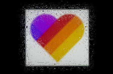 Heart with multi-colored stripes on a black background. Abstract photo of a heart with rainbow colors