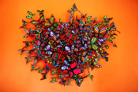 Butterflies heart shape grouping on orange background