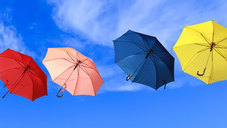 Flying colorful umbrellas into blue sky background