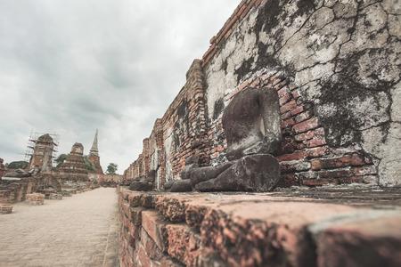 Ruined Buddha statue in Wat Mahathat, Ayutthaya historical park, Thailand.