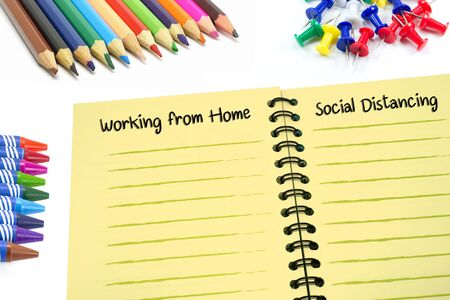 Working from home and Social distancing texts on notebook with colorful supplies on white background. Banco de Imagens