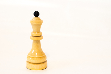 The white chess queen of wood on the white background
