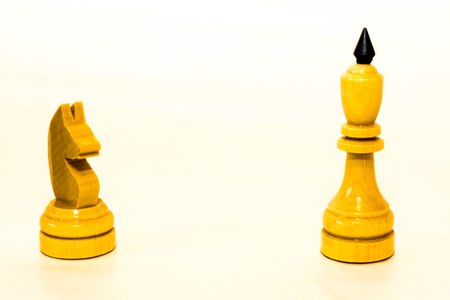 chessman: The white chess knight and the king of wood on the white background