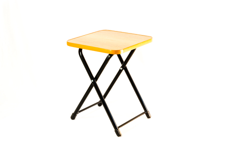 collapsible: The small square stool on the white background. The stool is isolated on white and a clipping path is provided for easy extraction. The stool is portable and its ideal for picnic and outing. Stock Photo