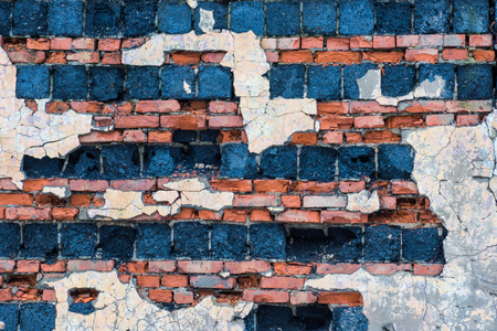 The old building wall of red bricks and blocks with the parts of plaster