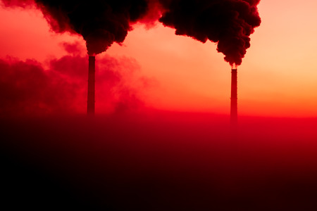 The silhouettes of the steaming pipes on the background of scarlet sunrise