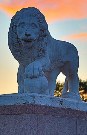 The statue of a lion holding his paw on the bowl in the park on the background of the sunset in the white night in Petersburg, Russia. Lions are the simbols of Petersburg. Stock Photo - 102948680