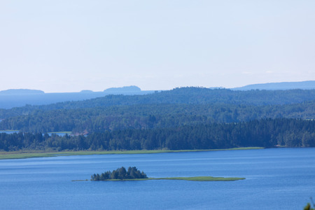 The island in the Ladoga lake in Russia with the mountains and the forest on the skyline in the sunny summer day