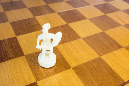 The isolated white chess pawn of stone or plastic on the square wood board