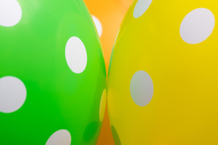 Background of green. orange and yellow balloons with the white circles on them. The optimistic picture, the symbol of happiness and joy
