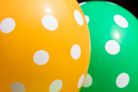 Background of green and orange balloons with the white circles on them. The optimistic picture, the symbol of happiness and joy