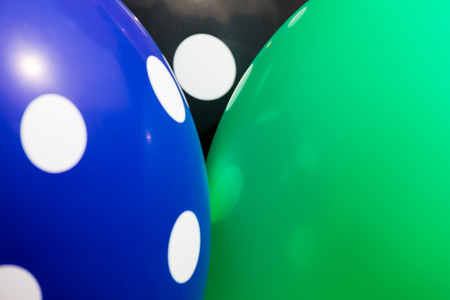 Background of blue, green and black balloons with the white circles on them. The optimistic picture, the symbol of happiness and joy