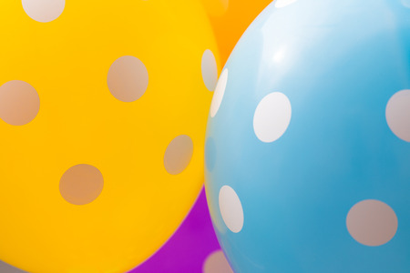 Background of orange, blue and purple balloons with the white circles on them. The optimistic picture, the symbol of happiness and joy