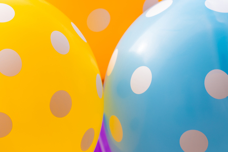 Background of blue, orange and yellow balloons with the white circles on them. The optimistic picture, the symbol of happiness and joy