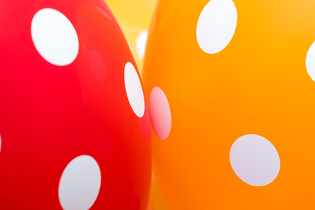 Background of red, orange and yellow balloons with the white circles on them. The optimistic picture, the symbol of happiness and joy