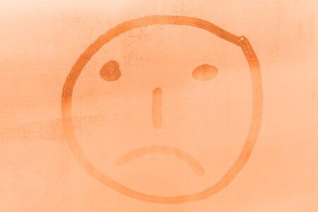 Figure of the sad face on the orange window Stock Photo